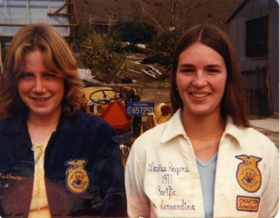 A pair of young women stand in front of agricultural buildings and a tractor. They wear jackets,  one blue and the other cream, with an insignia on the left breast and stitching on the right