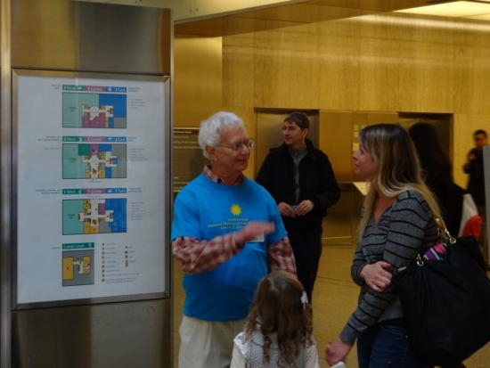 An ambassador in a blue shirt stands by the museum map and helps a mom and daughter