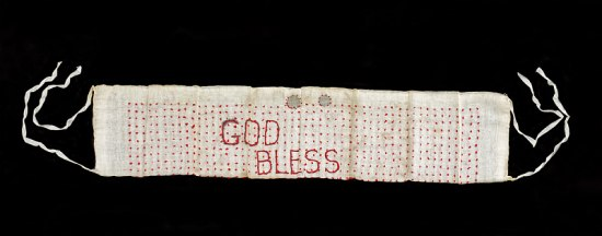 "A white sash with red dots in rows and ""God Bless"" stitched on. It has a couple of ties on each side and some coins at the top"