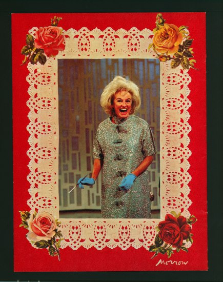 A color photograph of a blond woman in a shift with buttons down the front, a cigarette, and blue gloves. She is laughing on what appears to be some sort of television set with 70s decorations behind her. The picture is bordered by cream lace with illustrated flowers stuck on each corner. This is set on a bright red background.