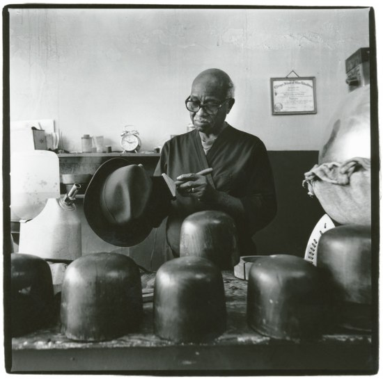 Photograph of Harold Cotton in his Greensboro, North Carolina shop. Cotton cleans a fedora with a brush. A group of hat blocks sit in the foreground, and Cotton's diploma hangs on the wall behind him.