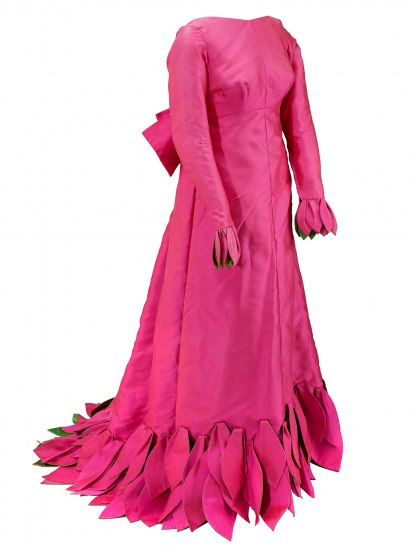 A satiny fuschia dress with a high neck, long sleeves, and a large skirt that looks like it is covered at the ends with petals, which also appear on the ends of the sleeves.