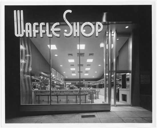 "A black and white photo of a storefront with a large electric sign above the glass front reading ""Waffle Shop."" A lunch counter with chrome swivel chairs can be seen inside."