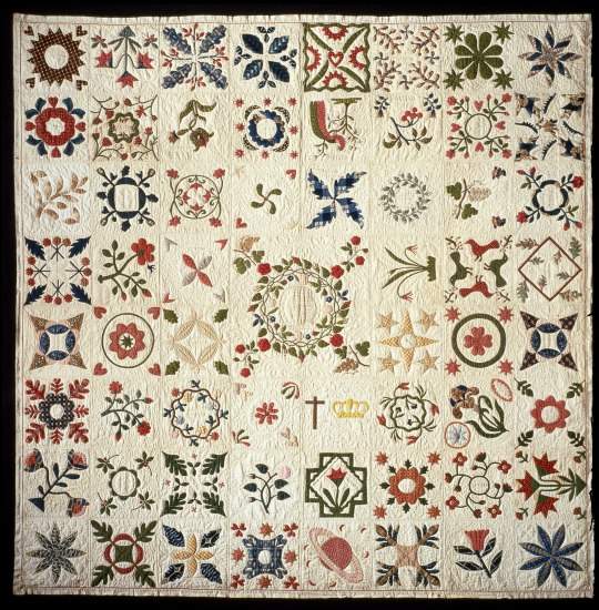 Quilt with white background and simple shapes in a variety of colors. These include flowers, leaves, and shapes.