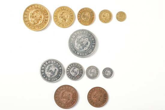 A range of brown, silver, and gold colored coins organized in rows