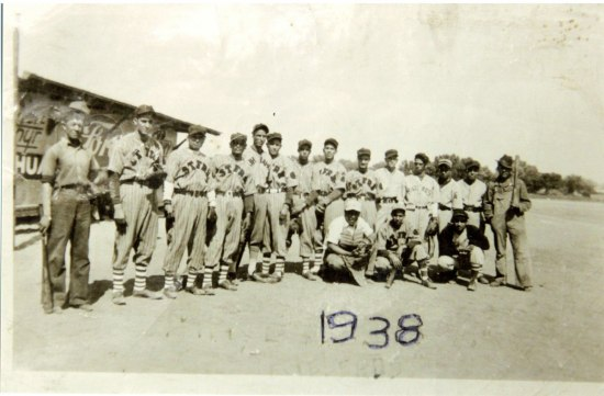 Martinez and his Chihuahua, Mexico baseball team pose in their uniforms on the field. On the front of the photo, someone has written the text: 1938.