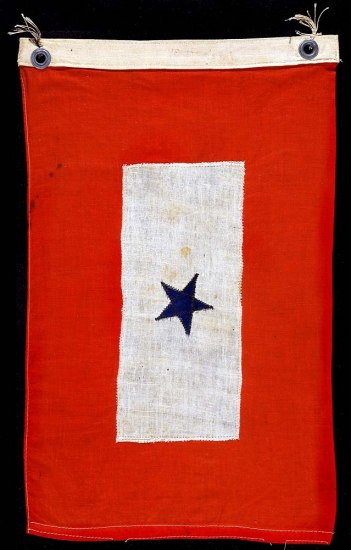 Red flag with white rectangle in center and blue star.