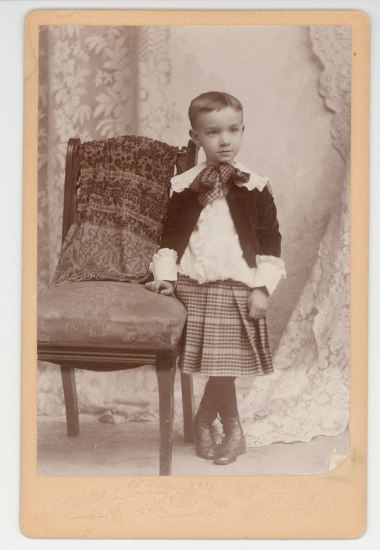 A young boy stands with his legs crossed and his hand on an upholstered chair. He wears a kilt with a blousy shirt and black jacket