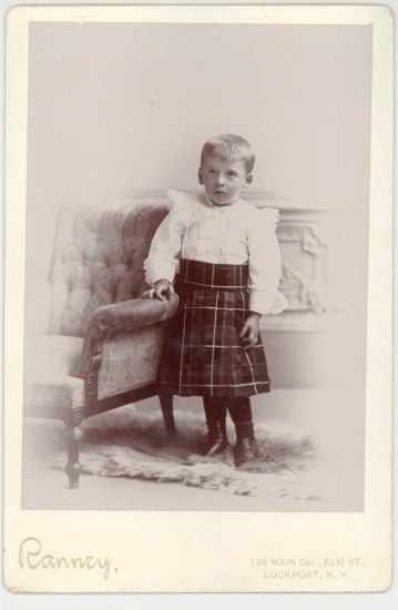 A very young boy stands next to a chair wearing a dark tartan kilt and a white frilly shirt tucked in.