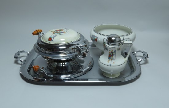 Several objects on a metal tray with handles. One is round and silver with a white top and small wooden handles. There is a china white bowl with illustrations and a small white pitcher with silver cap
