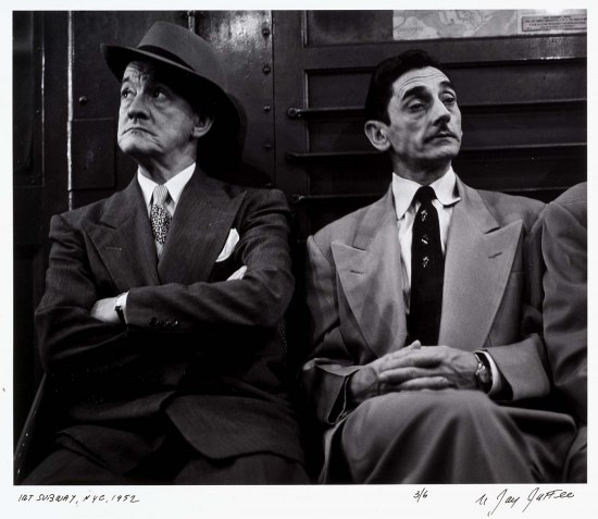 Two men in suits and ties, sit side by side in a subway car, staring in opposite directions. One wears a hat at a jaunty angle.