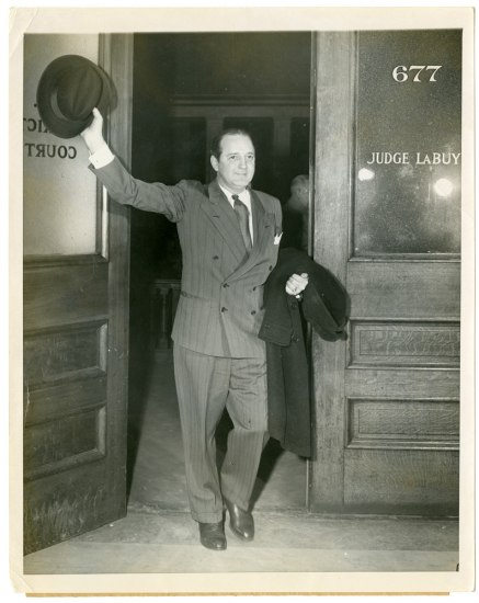 Photograph of Preston Tucker leaving courtroom, holding his hat above his head in victory.