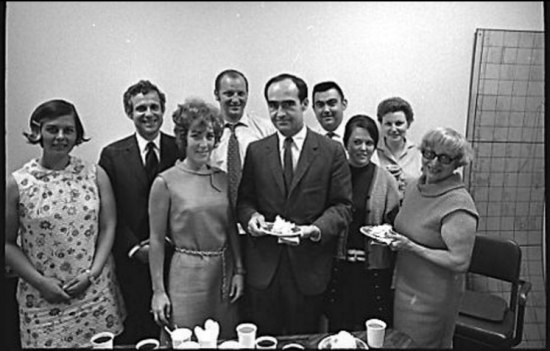 A black and white photograph of an office party from the 1960s. People in work attire hold plates with food on them as they gather around a table littered with cups and plates.