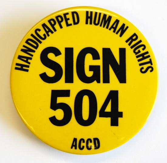 "Yellow button with text saying in capitalized letters ""Handicapped Human Rights: Sign 504 ACCD"" in bold text."