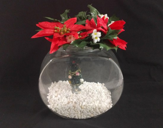 Photograph of a fish bowl with white gravel in the bottom, a small Christmas tree decoration, and a poinsettia flower (plastic) on top.