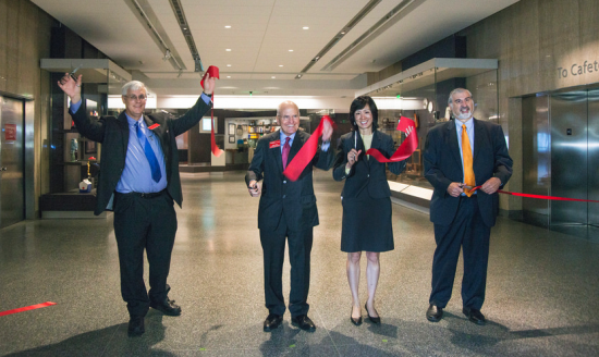 Photo of four people in formal dress having just cut a red ribbon to a museum space, smiles all around.
