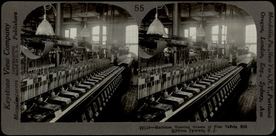 Stereograph (double) image in black and white. Machinery is shown making ribbons in a long room with tall windows and lamps hanging from ceiling. Factory.