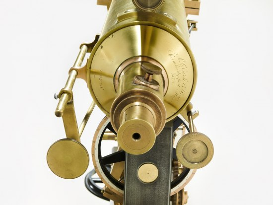 Photograph of one part of a telescope. It is gold in color. There is a circular part pointing right at the camera, perhaps where you might press your face to the telescope to look at the stars.