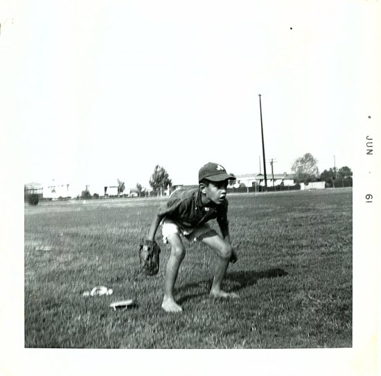Photograph of a young Eddie Martinez preparing to make a catch. Martinez stands barefoot, flip-flops by his side, crouched on the baseball field wearing a baseball cap and glove.