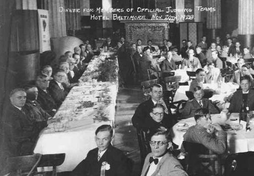 A black and white photograph of men at a banquet. There are long and round tables with white tablecloth and everyone appears to be dressed formally. Some writing on the top of the photo details the location and other information.