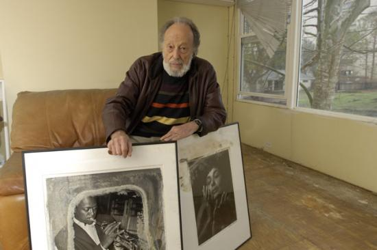 Man sits on couch, looking at camera with neutral expression. Leaned against his legs are large framed photos of jazz personalities.