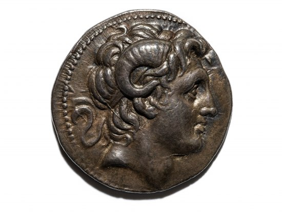 Bronze coin with a man's face on it. He has curly hair and rams' horns
