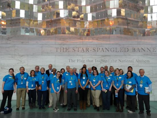 Group photo of ambassadors in blue shirts in museum lobby