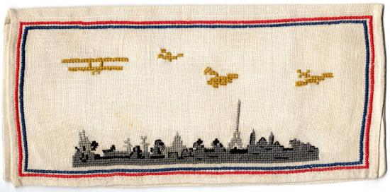 Photo of embroidery with scene of airplanes flying over a cityscape