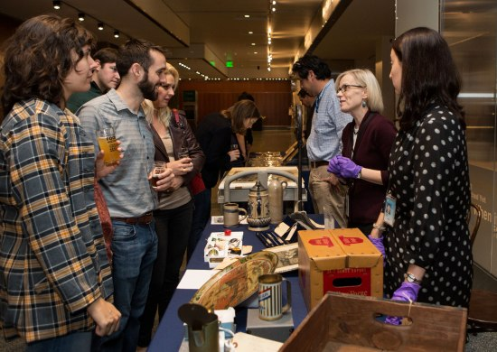 Visitors speak to curators with museum objects on display