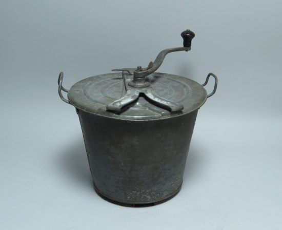 A silver-colored metal pot with handles on each side. There is a lid with a hand crank attached.