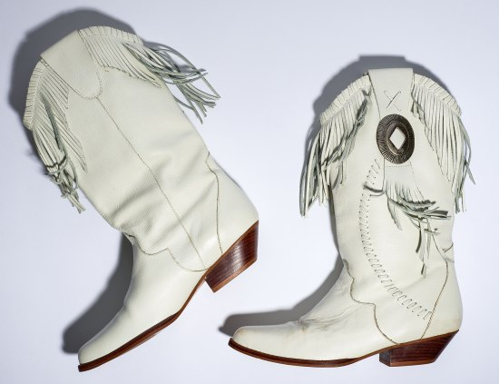 A pair of white leather cowboy boots with fringe