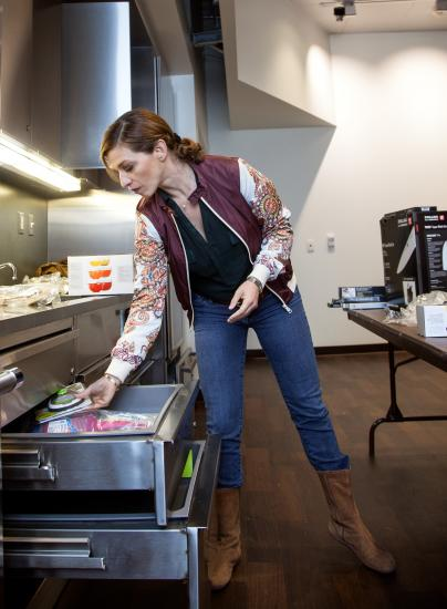 Woman in jeans leans over a kitchen drawer, which is open. She places a kitchen tool into the drawer. On the table, boxes sit to be unpacked.