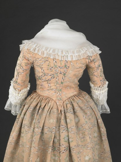 A photo of the back of a pink gown on a form. The pink gown has long sleeves with elaborate white ruffles. There are also ruffles and a shawl-like cowl around the neckline. The gown has white and light green details that appear to be interweaving ivy or ribbons.