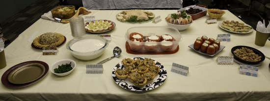 On a table covered in a beige table cloth, there are a number of potluck-style dishes laid out on plates and in bowls and Tupperware. Many of the dishes come in bite-sized portions, like deviled eggs, or with crackers. Each one has a festive name tag propped up next to it.