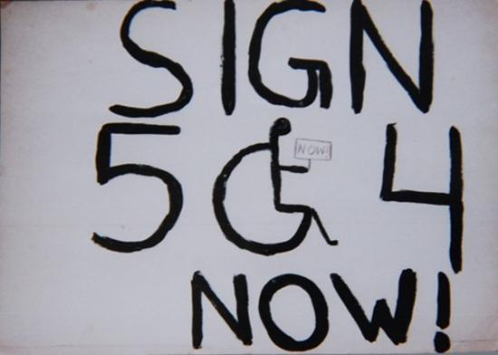 "Hand-written letters on white background saying ""Sign 504 now!"" The zero in the number ""504"" is the handicapped symbol (person in wheel chair)."