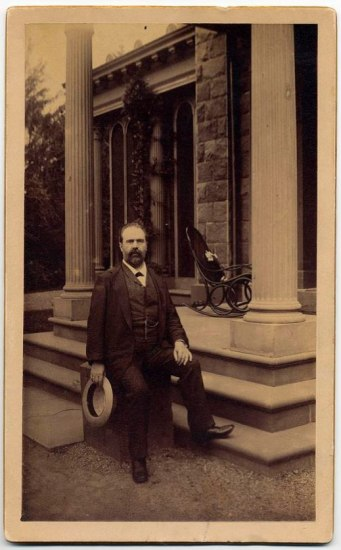 Black-and-white full-length portrait photo of a man on porch. Behind him is a rocking chair. His right leg is up on a step and he leans against a column. He has a beard and has removed his hat.