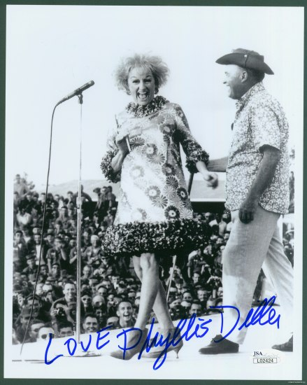 Black and white photograph of man and woman outside on stage in front of a crowd of men. The woman looks gleeful as she stands by a microphone.