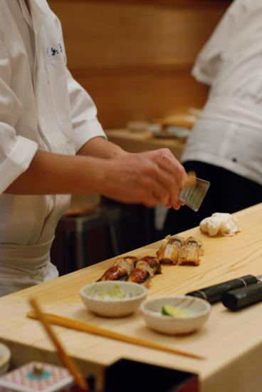A chef's hands, preparing sushi with ingredients in small bowls