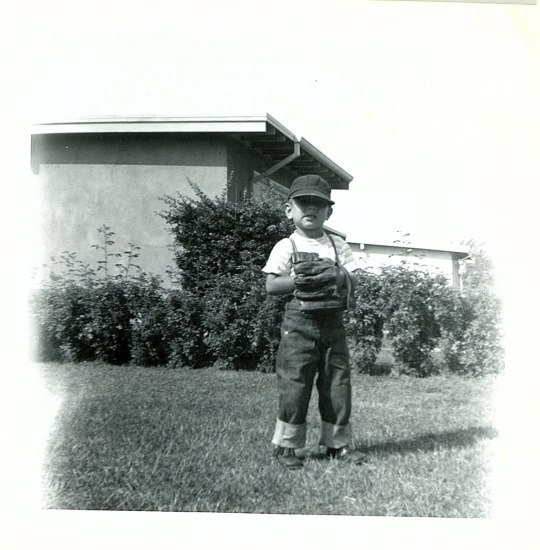 Photograph of toddler Howard Martinez posing in a front yard wearing a baseball cap and glove.