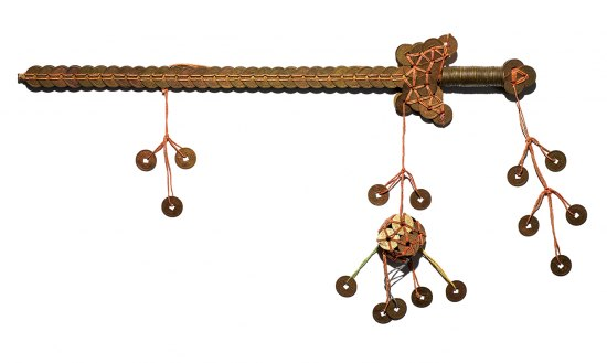A sword object that is made out of coins. They are copper-y in color with square holed in the middle. They are bound together with red string.