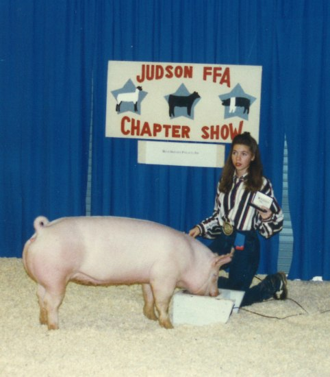 A young woman kneels on straw in front of a blue backdrop behind a large pig that is eating from a white container. There is a white sign hanging in front of the blue fabric and she poses with something in her left hand.