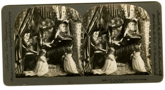 Stereo card shows two young girl posed in prayer in front a memorial for three assassinated presidents.