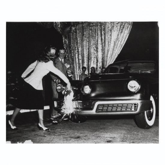 Photograph at a Tucker sedan publicity event. A woman breaks a bottle of champagne on the front fender of a sedan.