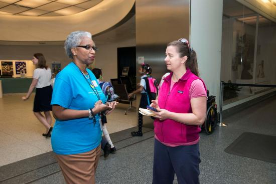 Ambassador speaks to visitor near museum Welcome Center