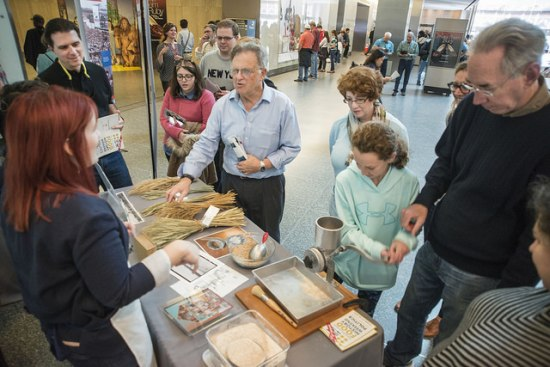 Museum visitors around a wheat mill demonstration table