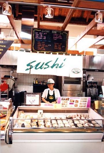 Employee behind sushi counter at grocery store