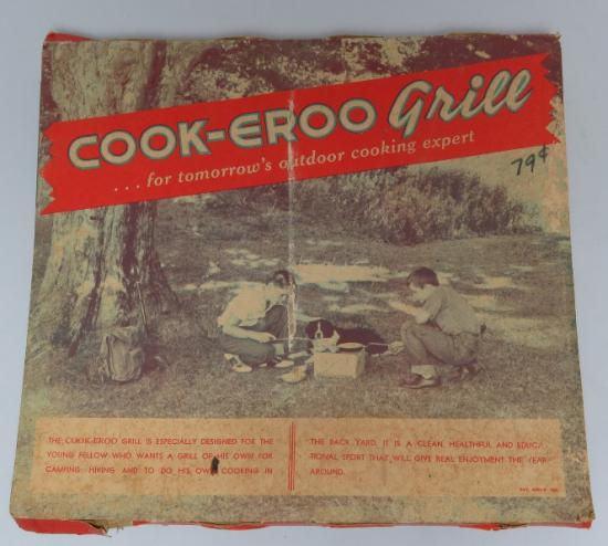 Box containing Cook-Eroo Grill. Image shows little boy and little girl with dog squatting on grass, grilling a meal. Under a tree.