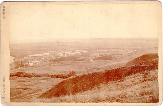 A photograph that depicts a fort and compound in a valley. It is sepia-colored.