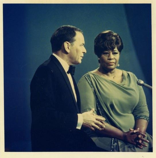 Frank Sinatra and Ella Fitzgerald sit in front of a microphone in performance dress. Frank looks like he has just said something and Ella sits impassively