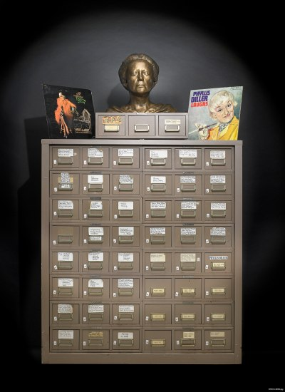 A view from the front of a large, medium brown file cabinet comprising many smaller drawers with labels on the outside. The bust of a woman with short hair sits on top and is flanked by two vinyl album covers portraying a woman with light colored hair